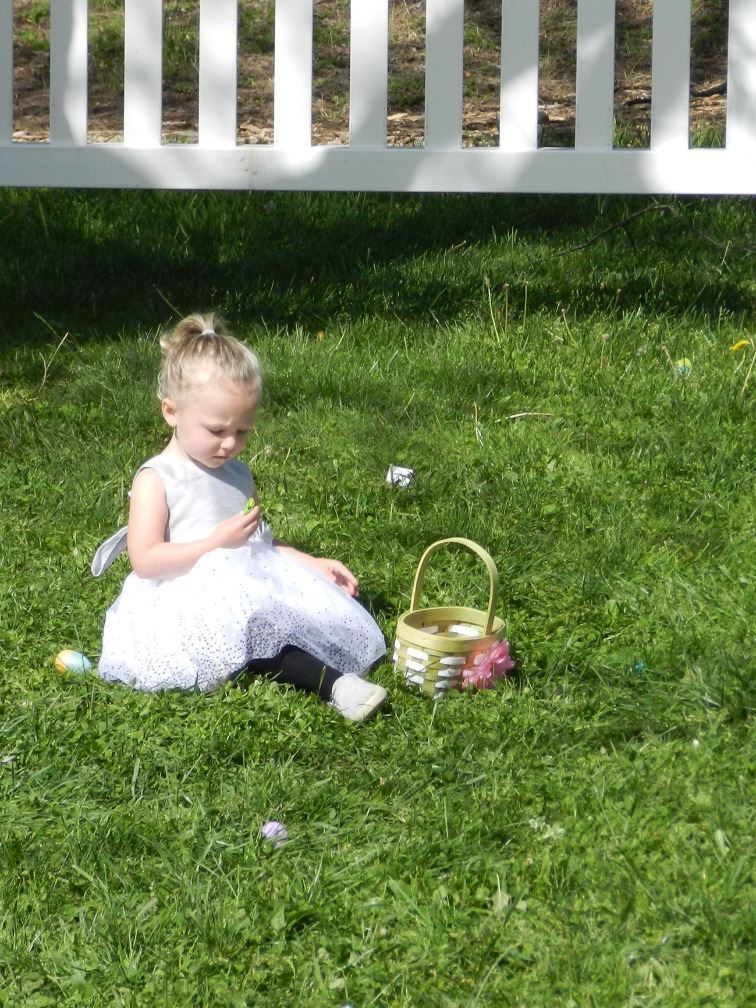 small girl sitting in grass with Easter basket