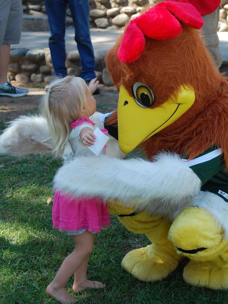 girl and mascot rooster hugging